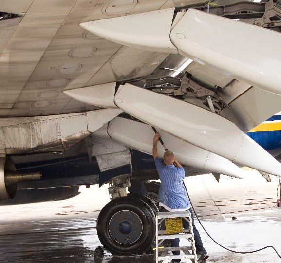 Image of line crew washing belly of jetliner.